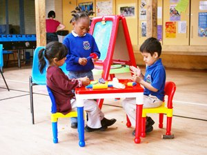 Three children with plastic classroom furniture